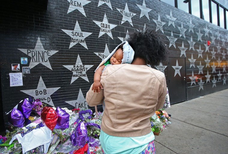 "Shanika Haynes looks at the Prince star and memorials as she carries her sleeping baby King Haynes outside First Avenue, Friday, April 22, 2016 in Minneapolis. Prince, widely acclaimed as one of the most inventive and influential musicians of his era with hits including ""Little Red Corvette,"" ''Let's Go Crazy"" and ""When Doves Cry,"" was found dead at his home on Thursday in suburban Minneapolis, according to his publicist. He was 57. (Elizabeth Flores/Star Tribune via AP)"