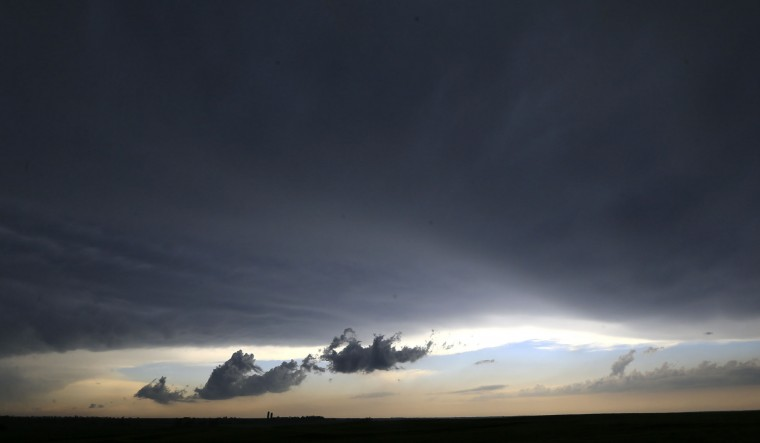 A low cloud moves over a farm near Gypsum, Kan., Tuesday, April 26, 2016. Thunderstorms bearing hail as big as grapefruit and winds approaching hurricane strength lashed portions of the Great Plains on Tuesday. The area is expecting severe weather. (AP Photo/Orlin Wagner)