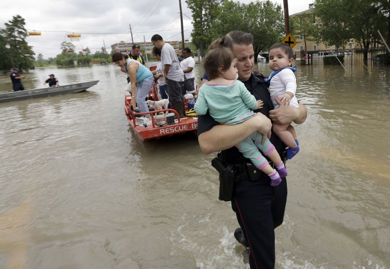 Harris County Constable Deputy J. King carries two children after they were evacuated from their flooded apartment complex, Tuesday, April 19, 2016, in Houston. Storms have dumped more than a foot of rain in the Houston area, flooding dozens of neighborhoods. (AP Photo/David J. Phillip)