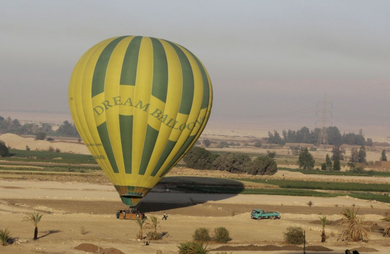 In this picture taken from a balloon Friday, April 1, 2016, a hot air balloon lands as the ground crew secures the balloon after a tour over the west bank of the Nile River, in Luxor, Egypt. They take off at first light, reinforced wicker baskets filled with people, heading into the skies over Luxor, Egypt. The ride lasts about 20 minutes, before the pilot begins looking for a safe landing zone. Tourists brace themselves for landing, a usually bumpy affair more akin to a soft crash landing. (AP Photo/Amr Nabil)