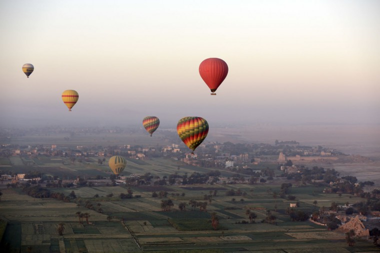 In this picture taken from a balloon Friday, April 1, 2016, hot air balloons fly over the west bank of the Nile River in Luxor, Egypt. The path of the brightly colored balloons is determined by prevailing winds. On the ride, the silence is broken only by the whoosh of the gas burners and the occasional exclamations from tourists awed by the sights. (AP Photo/Amr Nabil)
