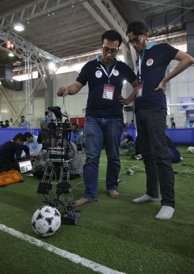 Iranian students from Amir Kabir university prepare their humanoid robot prior to a soccer match during the international robotics competition, RoboCup Iran Open 2016, in Tehran, Iran, Wednesday, April 6, 2016. (AP Photo/Vahid Salemi)