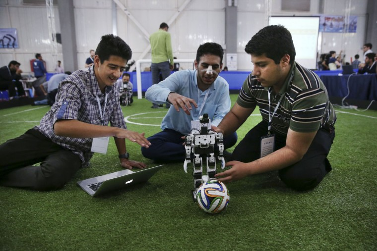 Iranian high school students prepare their humanoid robot prior to a soccer match during the international robotics competition, RoboCup Iran Open 2016, in Tehran, Iran, Wednesday, April 6, 2016. The event, organized by Iranian RoboCup Regional Committee and Qazvin Azad University, was participated by 320 teams from Iran and abroad. The 3-day competitions kicked off on Wednesday at Tehran's Permanent Fairground. (AP Photo/Vahid Salemi)