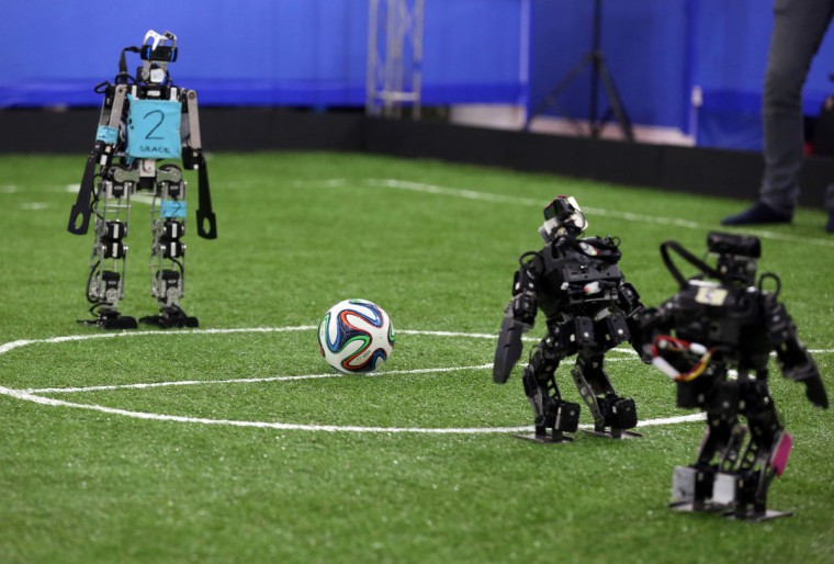 Robots from German FUmanoids team, of Berlin United University, and from Bit Bots team, of Hamburg University, take part in a soccer match during the RoboCup Iran Open 2016, in Tehran, on April 6. (ATTA KENARE/AFP/Getty Images)