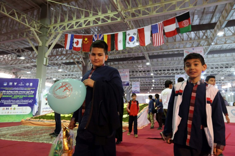 Iranian boys attend the RoboCup Iran Open 2016, in Tehran on April 6, 2016, as flags from countries attending the event, including the US, are seen decorating the venue. (ATTA KENARE/AFP/Getty Images)