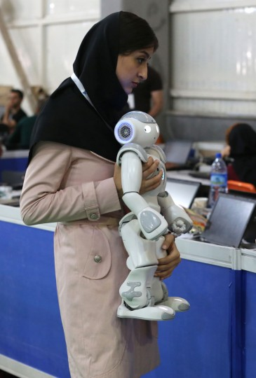 An Iranian woman from Iran's Qazvin Islamic Azad University carries a robot prior to a soccer match during the RoboCup Iran Open 2016, in Tehran on April 6, 2016. (ATTA KENARE/AFP/Getty Images)