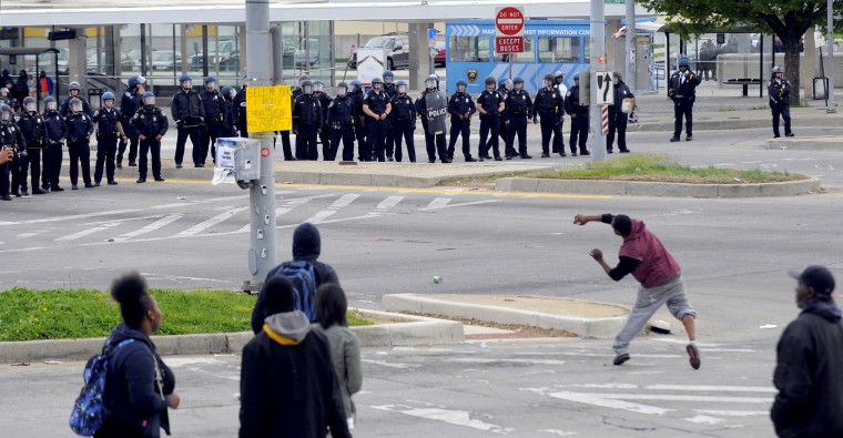 Outside bus and metro station at Mondawmin Mall, ayouth throws a stone at police officers lining the street.