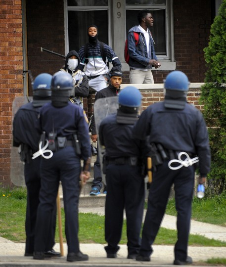 Baltimore police and protesters confront one another at a house near Mondawmin Mall. (Lloyd Fox/Baltimore Sun)