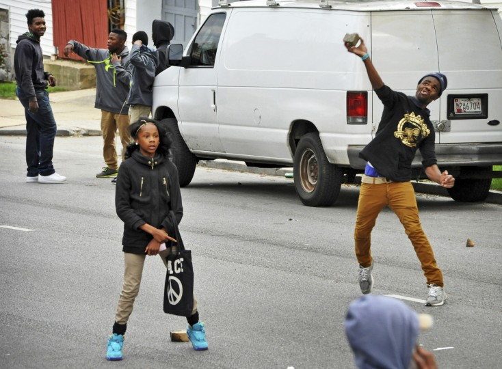 As youths stand nearby, an individual hurls a rock at the line of police on N. Monroe Street near Bryant Avenue. (Amy Davis/Baltimore Sun)