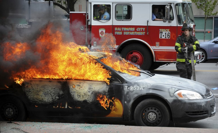 A Baltimore firefighter prepares to hose a Maryland Transit Authority patrol car burning at North and Pennsylvania avenues during the rioting April 27, 2015. (Jerry Jackson/Baltimore Sun)