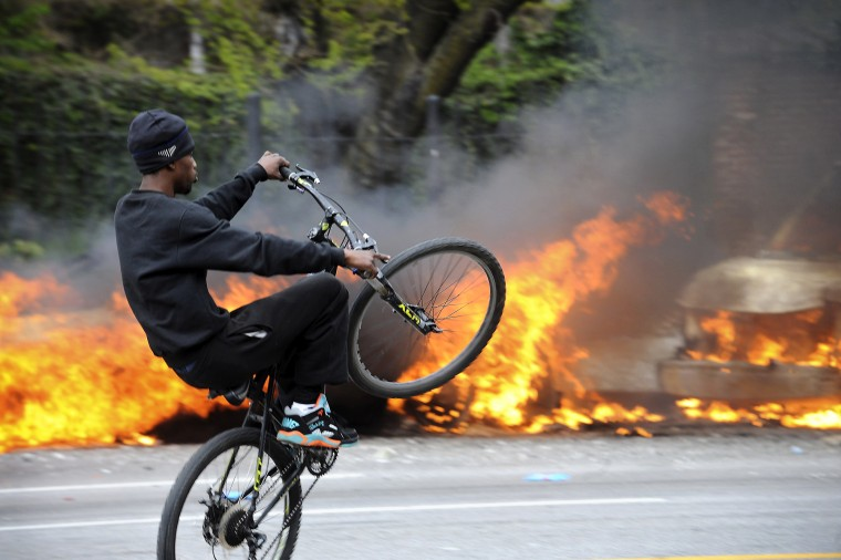 byclist rides in front of two burning police cars as riots break out in the Penn-North area of Baltimore on the day of Freddie Gray's funeral. Gray died from injuries sustained while in police custody. (Algerina Perna/Baltimore Sun)