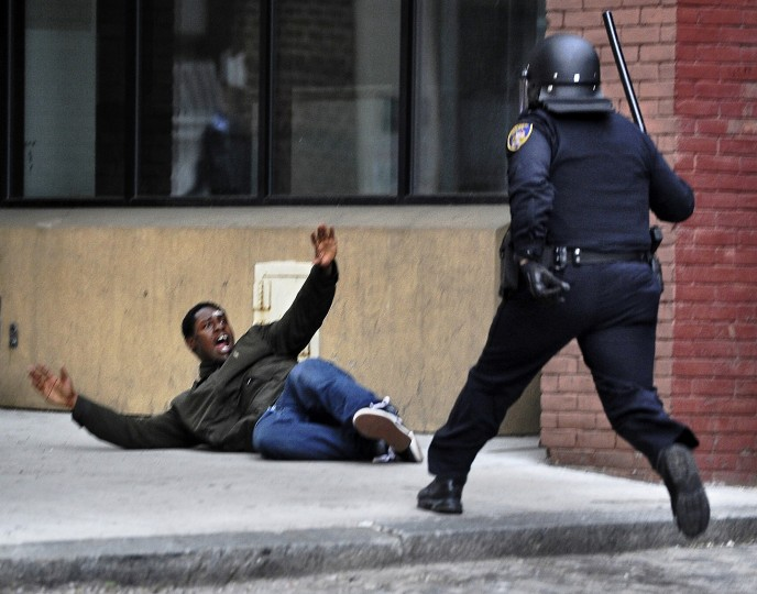 "A man screams ""Hands up!!"" after being chased by a police officer in downtown Baltimore near Lexington Market. The man, who police suspected of looting and property damage, was running from police before he fell and was arrested. The looting and unrest April 27, 2015, followed the burial of Freddie Gray, who died from injuries he sustained while in Baltimore police custody."