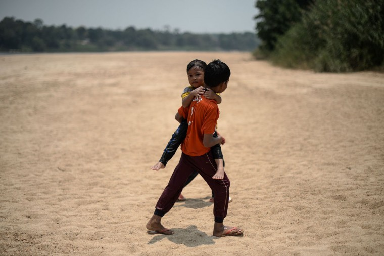 Children walk along the dry banks of the Pahang river as schools remain closed due to the ongoing heatwave in Termerloh, outside Kuala Lumpur, on April 11, 2016. (MOHD RASFAN/AFP/Getty Images)