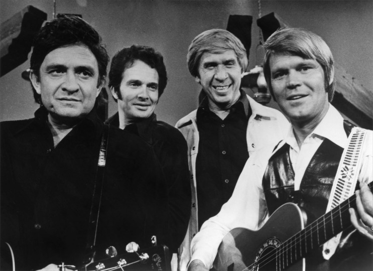 CIRCA MID 1970s: (L-R) Country musician Johnny Cash, Merle Haggard, Buck Owens and Glen Campbell perform on stage during a mid 1970's performance for a TV show. (Photo by Michael Ochs Archives/Getty Images)