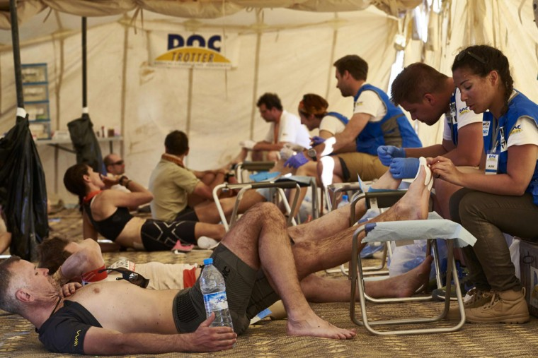 Competitors receive treatment for their feet during the second stage of the 31st edition of the Marathon des Sables On April 11, 2016 in the southern Moroccan Sahara desert. (JEAN-PHILIPPE KSIAZEK/AFP/Getty Images)
