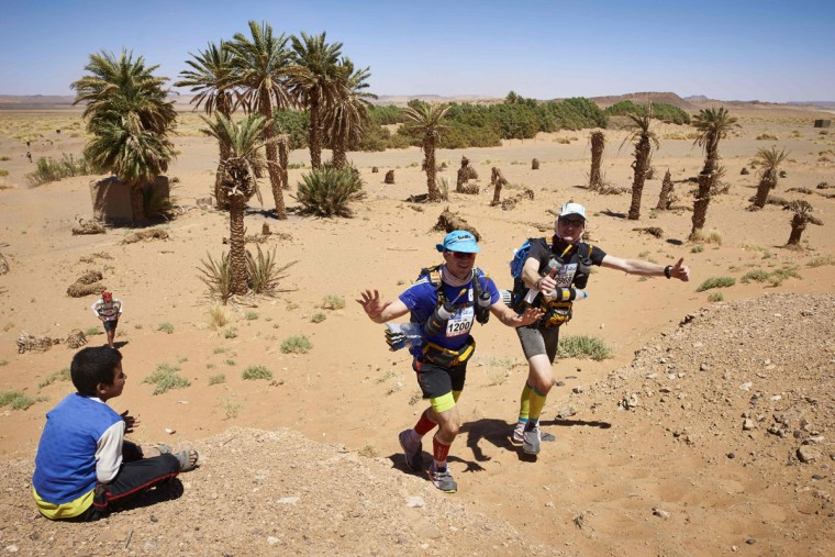 Competitors taking part in the 31st edition of the Marathon des Sables walk past a child in the village of Jdaid On April 11, 2016 in the southern Moroccan Sahara desert. (JEAN-PHILIPPE KSIAZEK/AFP/Getty Images)