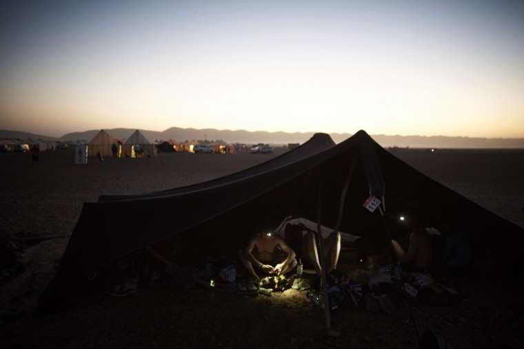 Competitors rest and eat at their bivouac during the 31st edition of the Marathon des Sables between Oued Moungarf and Ba Hallou in the southern Moroccan Sahara desert on April 12, 2016. (JEAN-PHILIPPE KSIAZEK/AFP/Getty Images)