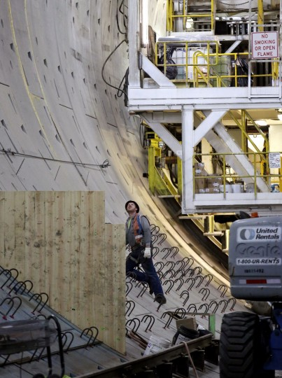 A worker looks up as he stands partway up a circular wall inside the State Route 99 tunnel that is under construction Monday, April 25, 2016, in Seattle. The Alaskan Way viaduct, which the two-mile tunnel will replace, is scheduled to be closed for about two weeks beginning Friday, April 29, as a precaution as tunnel boring begins under the structure. The tunneling machine is boring a double-decker traffic tunnel to replace the viaduct damaged in an earthquake in 2001. (AP Photo/Elaine Thompson)