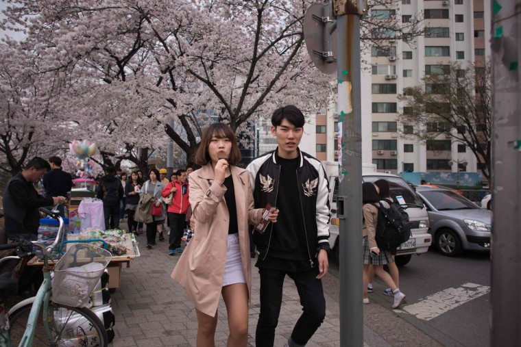 In a photo taken on April 6, 2016 a couple walk beneath cherry blossoms on Yeouido island in Seoul. The annual cherry blossom festival on Yeouido island in central Seoul runs from April 1-10. (ED JONES/AFP/Getty Images)