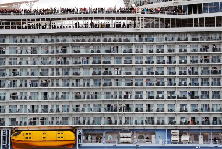 Passengers wave from the decks as the Harmony of the Seas cruise ship sets sail from Southampton, southern England, on May 22, 2016. (ADRIAN DENNIS/AFP/Getty Images)