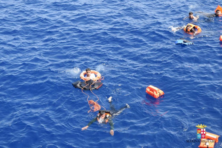 "This handout picture released on May 25, 2016 by the Italian Navy (Marina Militare) shows a rescue operation of the navy during the shipwreck of an overcrowded boat of migrants off the Libyan coast today. At least seven migrants have drowned after the heavily overcrowded boat they were sailing on overturned, the Italian navy said. The navy said 500 people had been pulled to safety and seven bodies recovered, but rescue operations were continuing and the death toll could rise. The navy's Bettica patrol boat spotted ""a boat in precarious conditions off the coast of Libya with numerous migrants aboard,"" it said in a statement. (AFP PHOTO / MARINA MILITARE)"