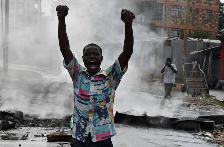A protestor gestures in Kibera slum during a demonstration of opposition supporters protesting for a change of leadership ahead of a vote due next years on May 23, 2016 in Nairobi. Local media reported at least one killed in Kisumu in the west of the country, while police in Nairobi and the second city of Mombasa fought running battles with small groups of protesters. There was no immediate police confirmation of the reported death. Police had banned the planned demonstrations and scores of officers in riot gear guarded the building that houses the election commission headquarters in the centre of the capital. (AFP PHOTO / CARL DE SOUZA)