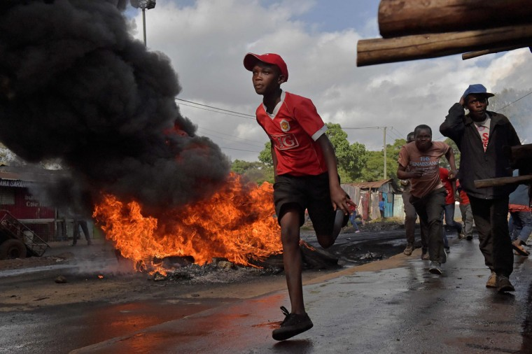A boy runs past a burning barricade in Kibera slum during a demonstration of opposition supporters protesting for a change of leadership ahead of a vote due next years on May 23, 2016 in Nairobi. Local media reported at least one killed in Kisumu in the west of the country, while police in Nairobi and the second city of Mombasa fought running battles with small groups of protesters.There was no immediate police confirmation of the reported death. Police had banned the planned demonstrations and scores of officers in riot gear guarded the building that houses the election commission headquarters in the centre of the capital. (AFP PHOTO / CARL DE SOUZA)