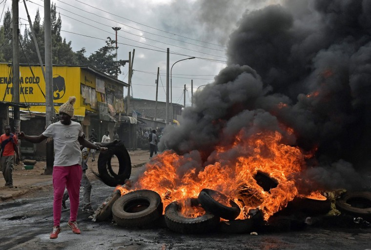 A protestor stands by a burning barricade in Kibera slum during a demonstration of opposition supporters protesting for a change of leadership ahead of a vote due next years on May 23, 2016 in Nairobi. Local media reported at least one killed in Kisumu in the west of the country, while police in Nairobi and the second city of Mombasa fought running battles with small groups of protesters. There was no immediate police confirmation of the reported death. Police had banned the planned demonstrations and scores of officers in riot gear guarded the building that houses the election commission headquarters in the centre of the capital. (AFP PHOTO / CARL DE SOUZA)