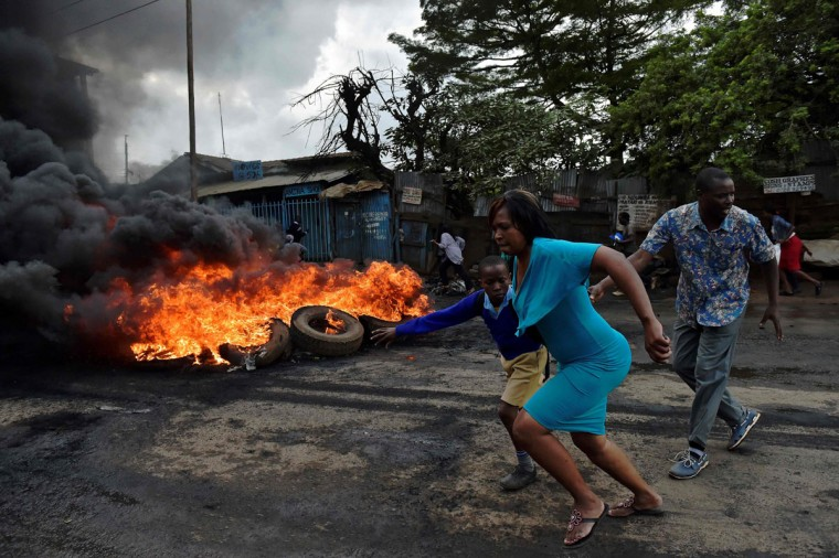 A woman leads a school pupil away from teargas and a burning barricade in Kibera slum, during a demonstration of opposition supporters protesting for a change of leadership ahead of a vote due next years on May 23, 2016 in Nairobi. Local media reported at least one killed in Kisumu in the west of the country, while police in Nairobi and the second city of Mombasa fought running battles with small groups of protesters. There was no immediate police confirmation of the reported death. Police had banned the planned demonstrations and scores of officers in riot gear guarded the building that houses the election commission headquarters in the centre of the capital. (AFP PHOTO / CARL DE SOUZA)