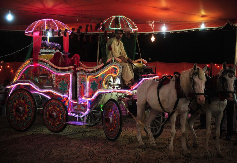 Pakistani brides arrive in a Baggi - horse drawn carriage - to attend a mass-wedding ceremony in Karachi late May 9, 2016. (ASIF HASSAN/AFP/Getty Images)