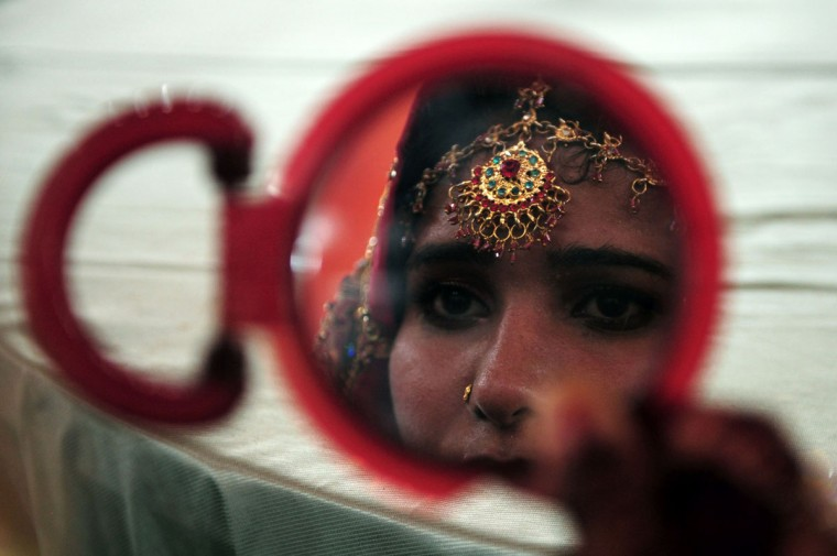 A Pakistani bride looks a mirror she attends a mass-wedding ceremony in Karachi late May 9, 2016. (ASIF HASSAN/AFP/Getty Images)