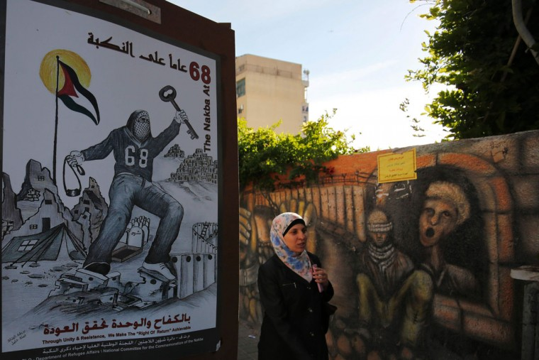 "A Palestinian woman walks past a poster depicting a key symbolising the keys to houses left by Palestinians in 1948, on May 11, 2016, in the West Bank city of Ramallah, a few days ahead the 68th anniversary of the ""Nakba"". ""Nakba"" means in Arabic ""catastrophe"" in reference to the birth of the state of Israel 68-years-ago in British-mandate Palestine, which led to the displacement of hundreds of thousands of Palestinians who either fled or were driven out of their homes during the 1948 war over Israel's creation. (AFP PHOTO / ABBAS MOMANI)"