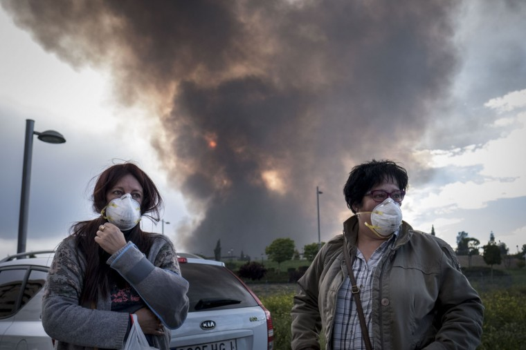 Two neighbours of Sesena wear masks as they wait for other relatives to evacuate a residential area affected by th toxic fumes produced by tyres burning in an uncontrolled dump near the town of Sesena, after a fire brokeout early on May 13, 2016. A huge tyre dump near Madrid was ablaze today, releasing a black cloud of toxic fumes and forcing the evacuation of nearby residents after what officials suspect was an arson attack. (AFP Photo/Pedro Armestre)