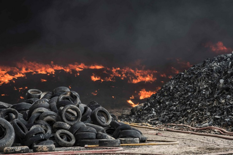 Tyres burn in an uncontrolled dump near the town of Sesena, after a fire brokeout early on May 13, 2016. A huge waste ground near Madrid where millions of tyres have been dumped was on fire today, releasing a thick black cloud of toxic fumes that officials worry could harm residents nearby. (AFP Photo/Pedro Armestre)