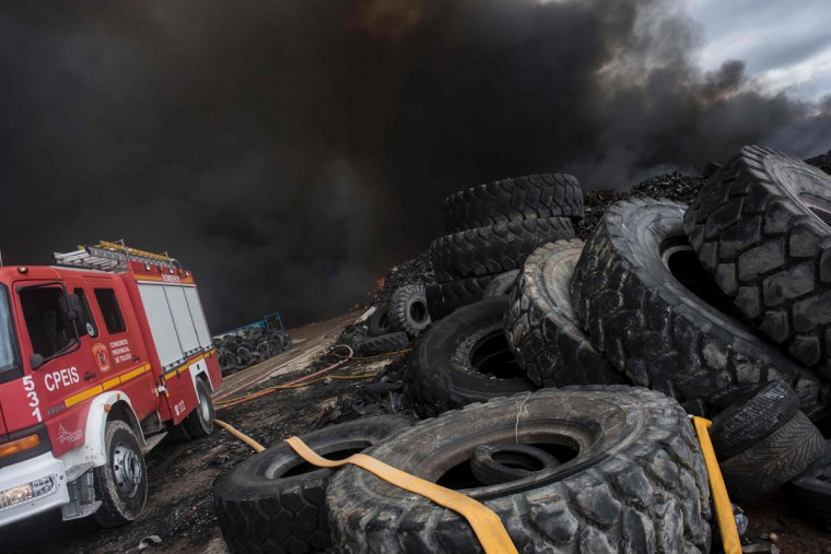 Clouds of dark smoke cover the sky as a fire truck works among piles of tyres in an uncontrolled dump near the town of Sesena, after a fire brokeout early on May 13, 2016. A huge waste ground near Madrid where millions of tyres have been dumped was on fire today, releasing a thick black cloud of toxic fumes that officials worry could harm residents nearby. (AFP Photo/Pedro Armestre)