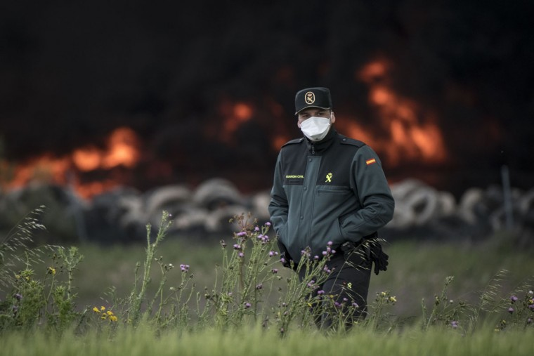 A civil guard with a mask walks past a pile of tyres burning in an uncontrolled dump near the town of Sesena, after a fire brokeout early on May 13, 2016. A huge waste ground near Madrid where millions of tyres have been dumped was on fire today, releasing a thick black cloud of toxic fumes that officials worry could harm residents nearby. (AFP Photo/Pedro Armestre)