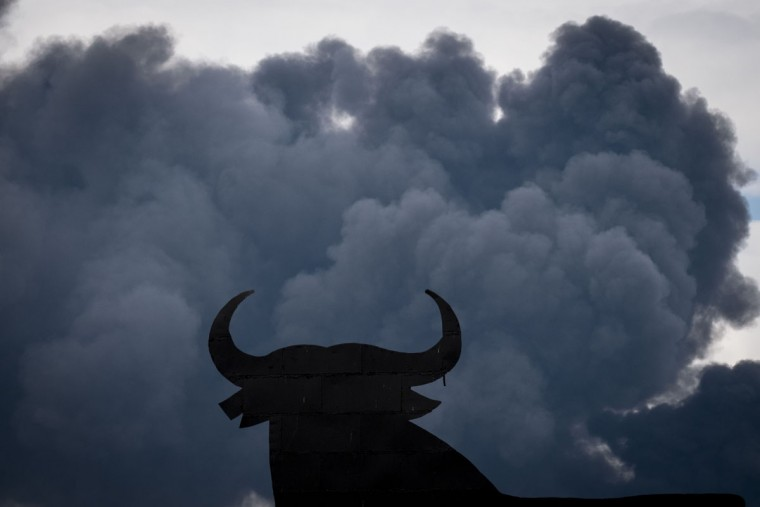 "The shape of an ""Osborne Bull"" is pictured with black clouds of smoke on the background, produced by tyres burning in an uncontrolled dump near the town of Sesena, after a fire brokeout early on May 13, 2016. A huge waste ground near Madrid where millions of tyres have been dumped was on fire today, releasing a thick black cloud of toxic fumes that officials worry could harm residents nearby. (AFP Photo/Pedro Armestre)"