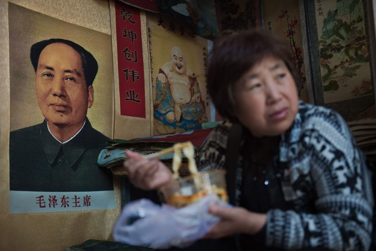 A vendor eats noodles next to a poster of late Chinese chairman Mao Zedong (L) at a market in Beijing on May 15, 2016. Fifty years after the Cultural Revolution spread bloodshed and turmoil across China, the Communist-ruled country is driving firmly down the capitalist road, but Mao Zedong's legacy remains -- like the embalmed leader himself -- far from buried. (AFP PHOTO / NICOLAS ASFOURI)