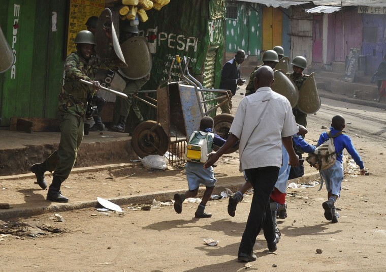 A man with his children walks past anti riot police dispersing opposition supporters demanding a change of leadership at the electoral commission ahead of a vote due next year, on May 23, 2016 in Nairobi. Local media reported at least one killed in Kisumu in the west of the country, while police in Nairobi and the second city of Mombasa fought running battles with small groups of protesters. There was no immediate police confirmation of the reported death. Police had banned the planned demonstrations and scores of officers in riot gear guarded the building that houses the election commission headquarters in the centre of the capital. (AFP PHOTO / SIMON MAINA)