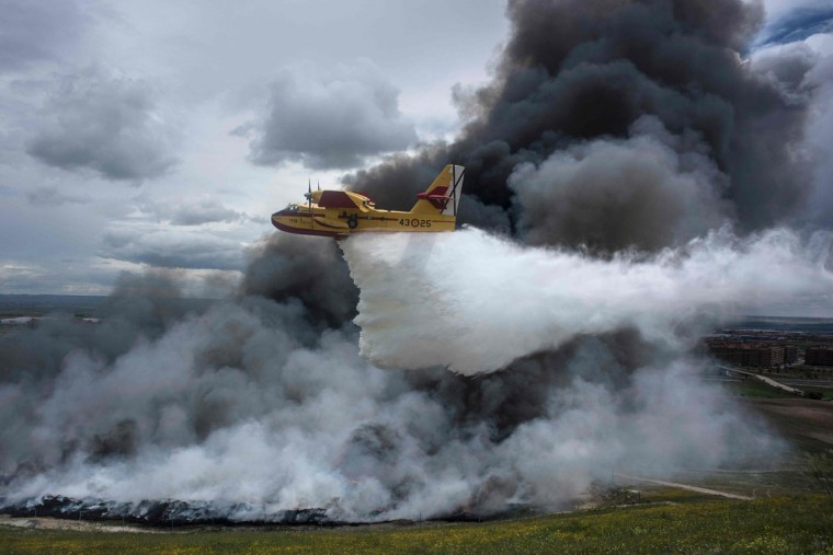 A seaplane discharges water over the tyres burning in an uncontrolled dump near the town of Sesena, after a fire brokeout early on May 13, 2016. A huge waste ground near Madrid where millions of tyres have been dumped was on fire today, releasing a thick black cloud of toxic fumes that officials worry could harm residents nearby. (AFP Photo/Pedro Armestre)