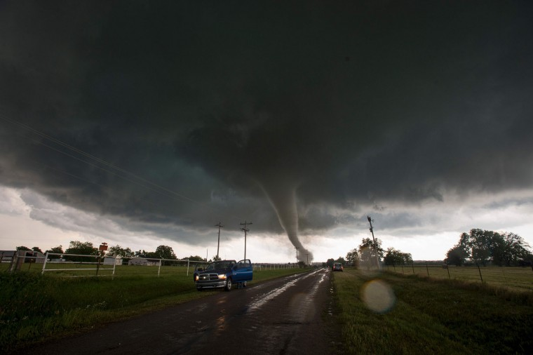 Vehicles stop on the side of a road as a tornado rips through a residential area after touching down south of Wynnewood, Oklahoma on May 9, 2016. The tornado touched down quickly and destroyed an unknown number of structures before a series of other twisters riddled the area. One person is confirmed dead. (Josh Edelson/AFP/Getty Images)