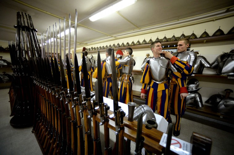 New Vatican Swiss Guards help each other as they adjust their uniforms prior to a swearing-in ceremony in Vatican City, on May 6, 2016. The annual swearing in ceremony for the new papal Swiss guards takes place on May 6, commemorating the 147 who died defending Pope Clement VII on the same day in 1527. (AFP Photo/Filippo Monteforte)