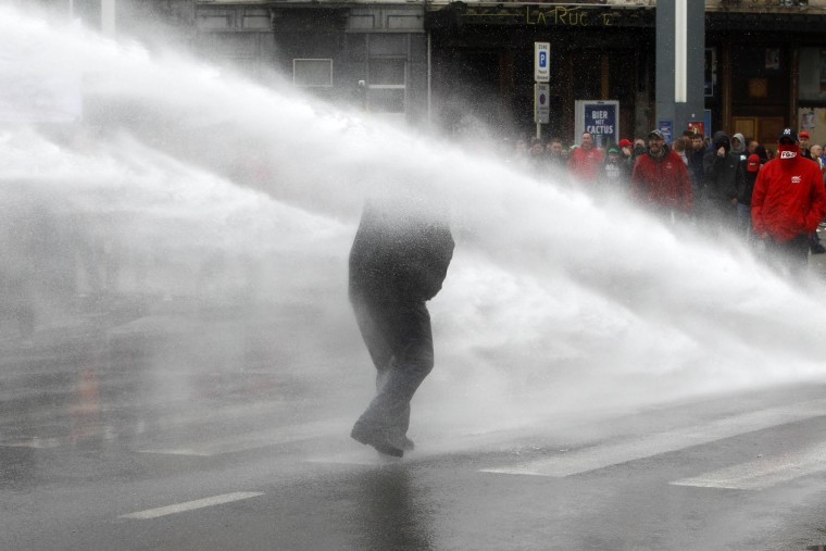 A protester is targeted by a water cannon during clashes with riot police during a demonstration against new working regulations in Brussels, Belgium, Tuesday, May 24, 2016. (AP Photo/Michel Spingler)