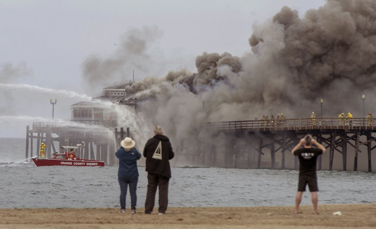 Spectators gather on the sand as fire boats and firefighters battle a fire on the Seal Beach pier in Seal Beach, Calif. on Friday, May 20, 2016. The blaze erupted early Friday at the end of the long wooden pier southeast of Los Angeles. Smoke was pouring out of holes in the roof, much of which had collapsed. The restaurant has been closed since 2013. (Michael Goulding/The Orange County Register via AP)