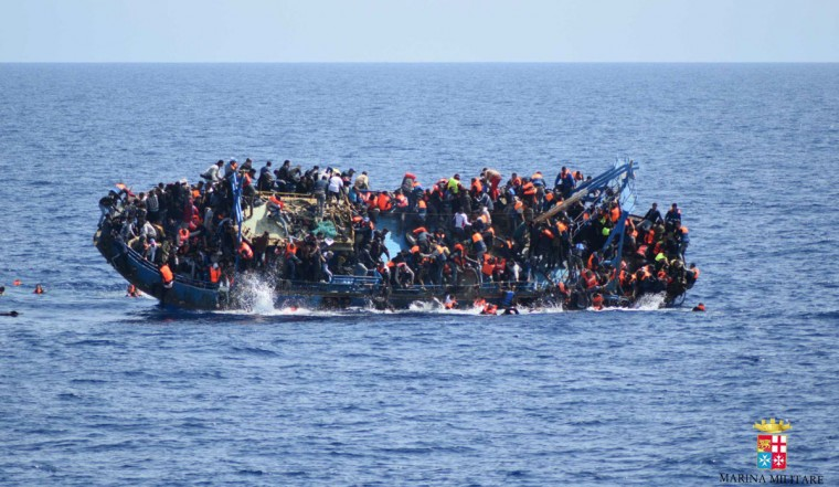 People jump out of a boat right before it overturns off the Libyan coast, Wednesday, May 25, 2016. The Italian navy says it has recovered 7 bodies from the overturned migrant ship off the coast of Libya. Another 500 migrants who on board were rescued safely. (Marina Militare via AP Photo)