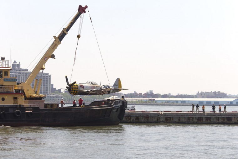 Officials place a plane on the Wall St. Heliport pier after removing it from the Hudson River a day after it crashed,, Saturday, May 28, 2016, in New York. The World War II vintage P-47 Thunderbolt aircraft crashed into the river Friday, May 27. (AP Photo/Mary Altaffer)