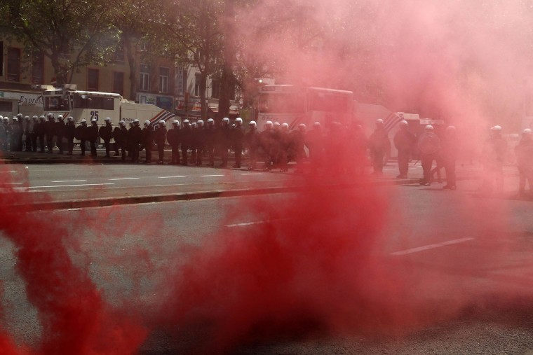 Riot police take position as demonstrators protest against new working regulations in Brussels, Belgium, Tuesday, May 24, 2016. Belgian riot police fired a water cannon at protesters Tuesday after fighting broke out at the end of a major anti-austerity demonstration attended by tens of thousands of people in central Brussels. (AP Photo/Michel Spingler)