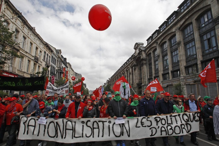 Union workers march during a protest against new working regulations in Brussels, Belgium, Tuesday, May 24, 2016. Belgian riot police clashed with protesters Tuesday at the end of a major anti-austerity demonstration attended by tens of thousands of people in central Brussels. The demonstration was called to protest against the center-right government's social and economic policies, which trade unions say cut deep into the foundations of Belgium's welfare state. (AP Photo/Michel Spingler)