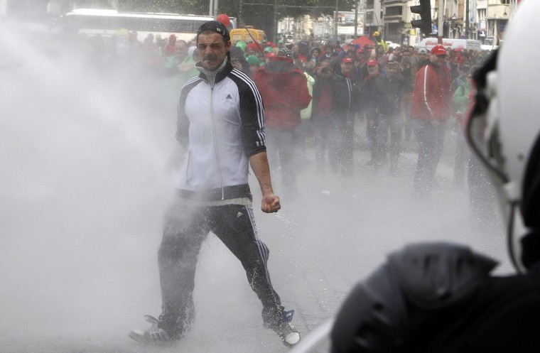 A demonstrator stands in front of a water cannon during clashes with riot police at a protest against new working regulations in Brussels, Belgium, Tuesday, May 24, 2016. Belgian riot police fired a water cannon at protesters Tuesday after fighting broke out at the end of a major anti-austerity demonstration attended by tens of thousands of people in central Brussels. (AP Photo/Michel Spingler)