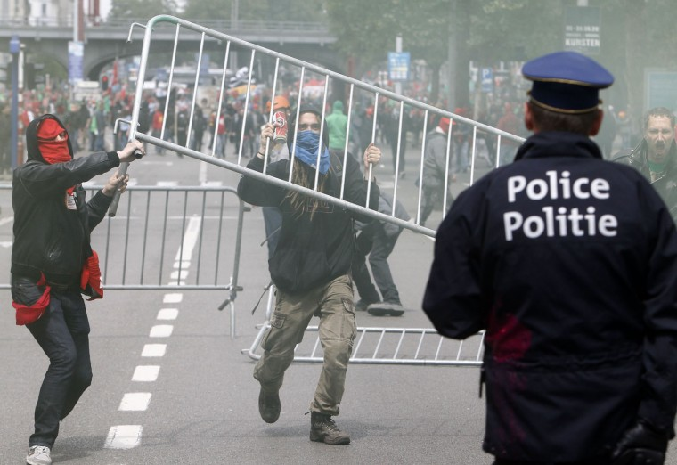 Masked protesters clash with riot police during a protest against new working regulations in Brussels, Belgium, Tuesday, May 24, 2016. Belgian riot police fired a water cannon at protesters Tuesday after fighting broke out at the end of a major anti-austerity demonstration attended by tens of thousands of people in central Brussels. (AP Photo/Michel Spingler)